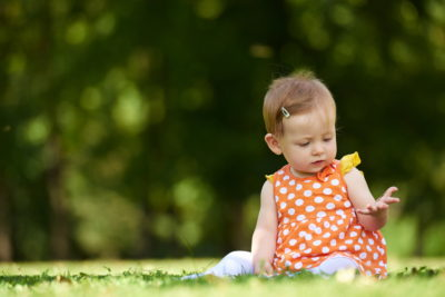 happy young baby child sittng on grass on beautiful summer day in park